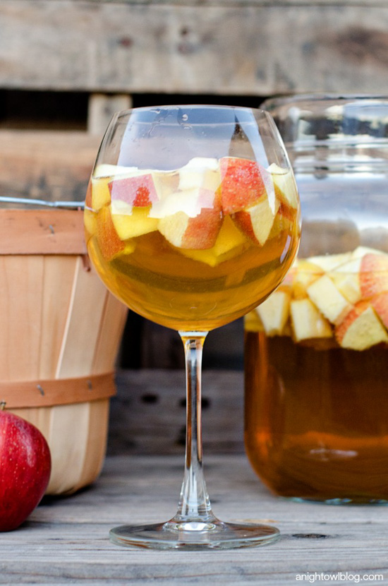 Large glass filled with apple sangria and a large jug of it in the background next to an apple picking basket.