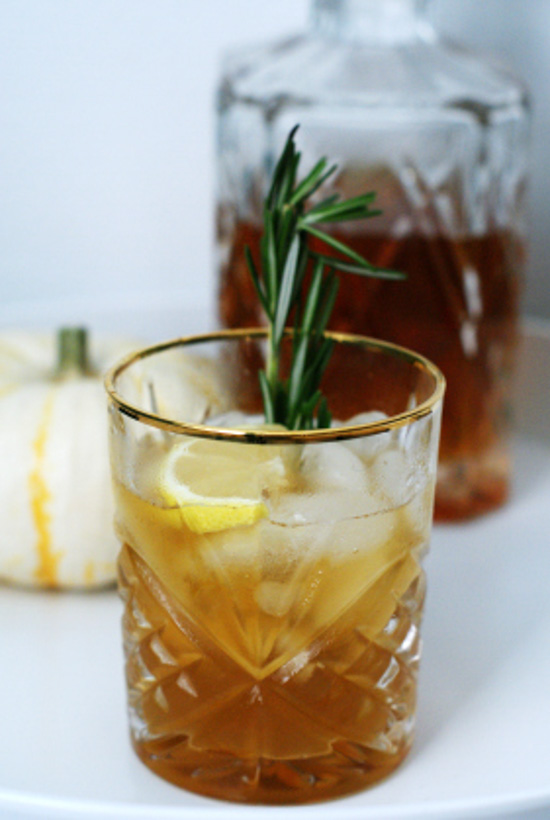 An etched tumbler with a gold-rim filled with a cocktail and a lemon and rosemary garnish with a decanter in the background.