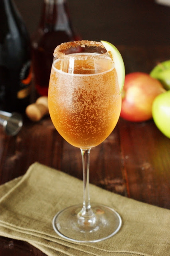 White wine glass with a sugared-rim, filled with sparkling peach colored liquid placed on a linen napkin with apples in the background.