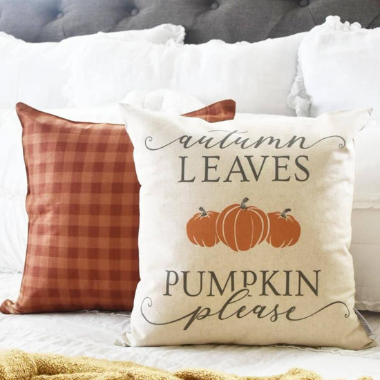 Fall finds these pillow covers displayed on a white and gray bed, one in orange gingham and one says', 'autumn leaves and pumpkin please'.