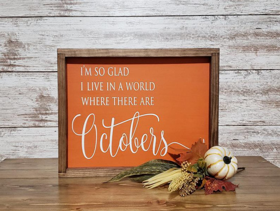 Rustic, farmhouse sign, wood frame and orange inlay that says, 'I'm so glad I live in a world where there are Octobers'.