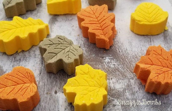 Small bath bombs in a variety of leaf shapes in shades of orange, yellow and brown.