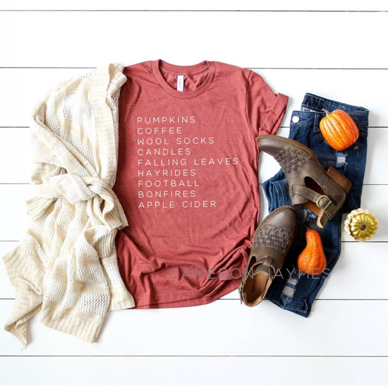 Fall outfit flat-lay. Cream sweater, t-shirt with a list of fall favorite things, dark denim jeans, brown booties and Halloween gourds plaid around them.