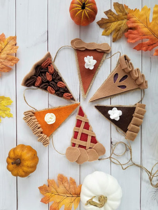 Felt bunting on twine each piece made to look like a different flavor of seasonal pie, and surrounded by autumn leaves and pumpkins.