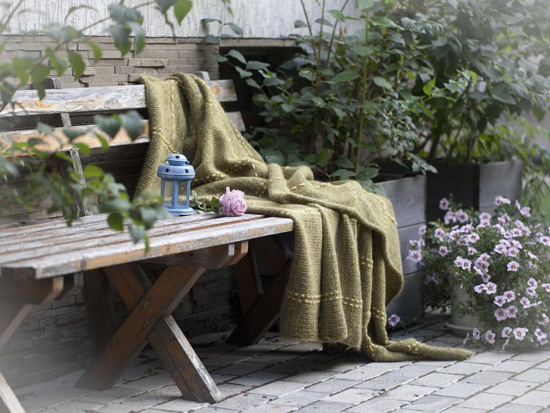 Hand-knit blanket in a muted shade of olive green laid over a rustic wooden bench and surrounded by foliage.