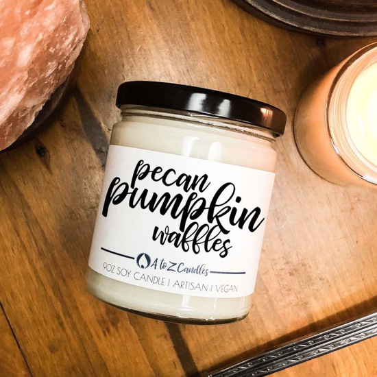 White candle in a glass container with a black lid in the scent 'pecan pumpkin waffles' placed on a wooden table with a burning candle next to it.