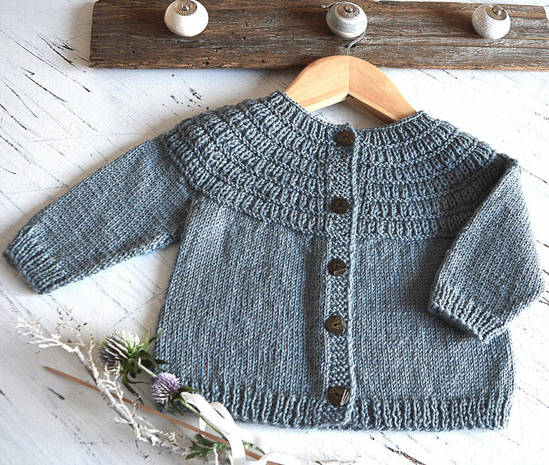 Gray button-down knit cardigan for a child, on a wooden hanger.