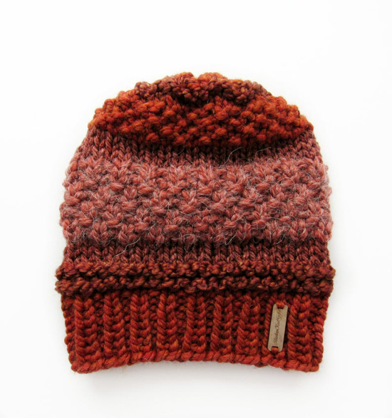Multi-textured beanie in shades of burgundy and burnt orange with a small metal sewn on tag.