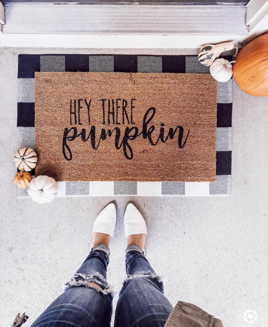 Halloween decor, jute rug with 'hey there pumpkin' written on it and laid over a black and white buffalo check surrounded by pumpkins and female legs wearing jeans and white flats.