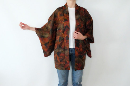 Woman wearing jeans and white top and modeling a kimono that looks like it's covered in fall foliage.