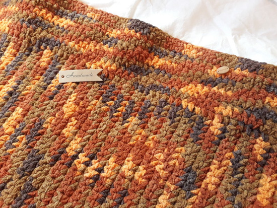 Multi-colored fall themed, knit chenille throw blanket.