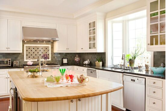 Open airy white kitchen with English Country Style and butcher block top island.
