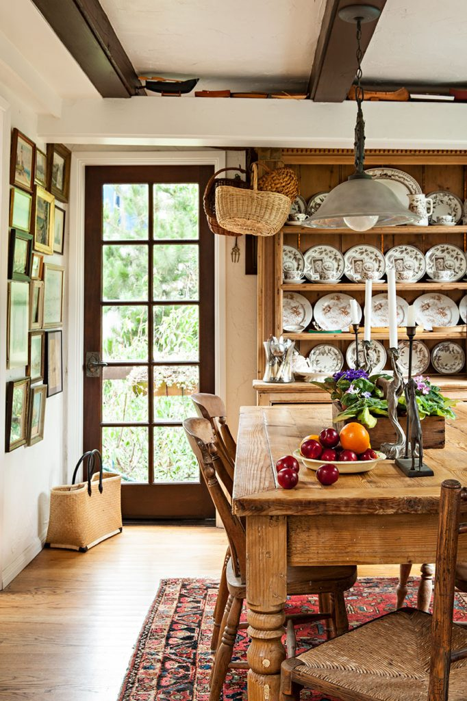 A rustic, farmhouse kitchen displaying a full china collection in a hutch and a substantial farmhouse table with wood and wicker chairs around it.