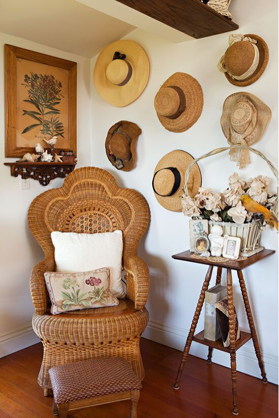 Vintage rattan peacock style chair and an accent wall covered in sun hats.