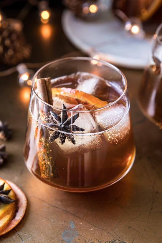 Fancy stemless glass filled with a caramel colored cocktail and garnished with an orange slice cinnamon stick.
