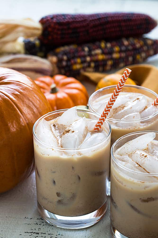 Three frothy cocktails in tumblers with orange and white straws, pumpkins and multi-colored corn in the background.
