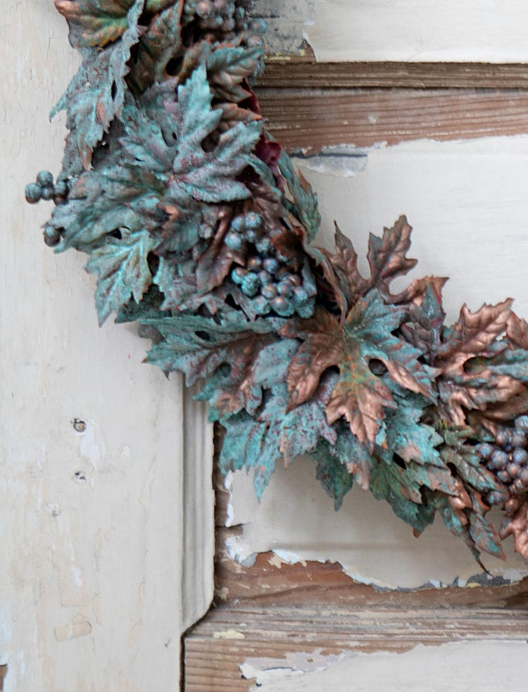 Close-up shot of a copper patina fall wreath on a door with white chipped paint