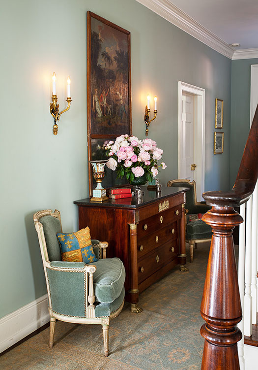 English Country entryway, complete with vintage furniture and a large oil painting flanked by wall sconces.