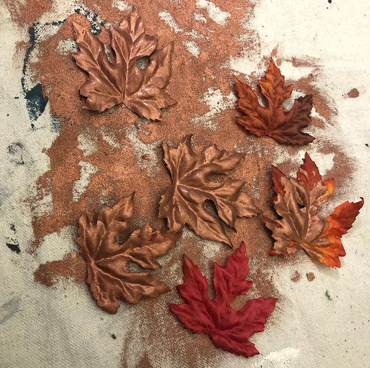Copper painted fall maple leaves on a dropcloth