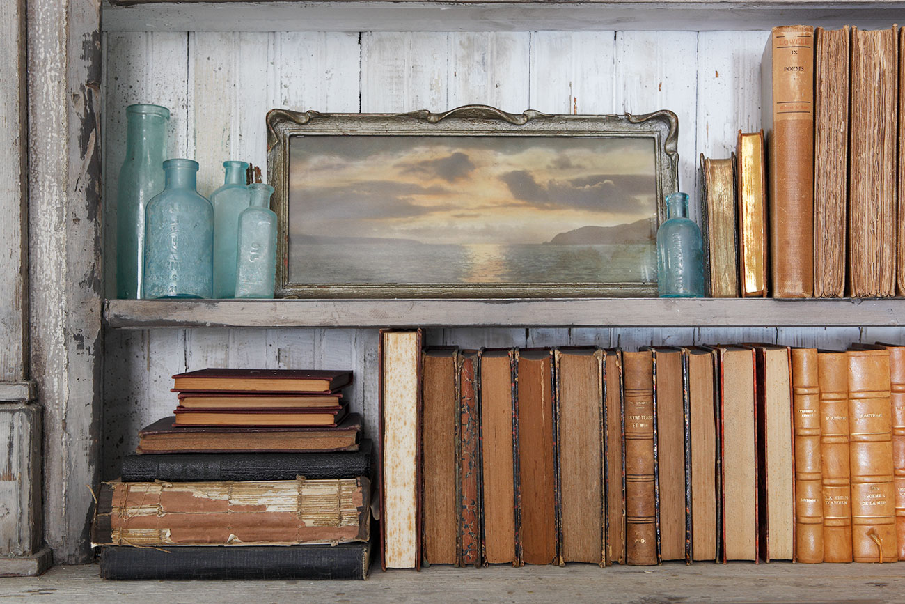 Bookshelves filled with art, aqua colored glass bottles and vintage books.
