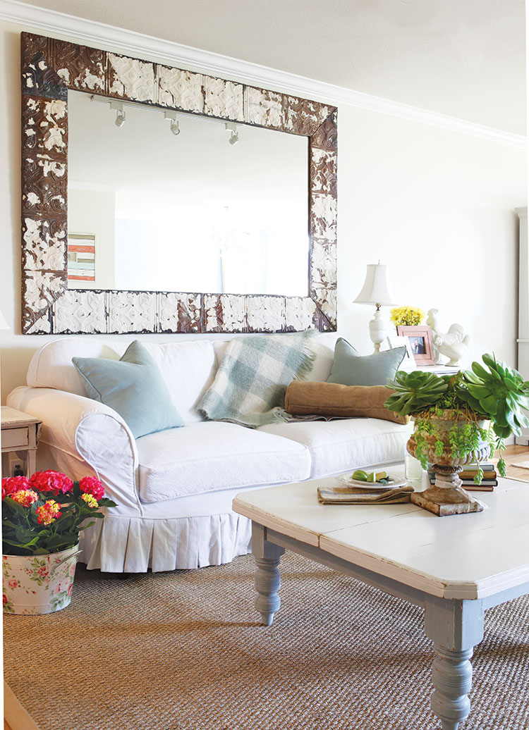 English Country style living room with cozy oversized white couch and white wooden coffee table.
