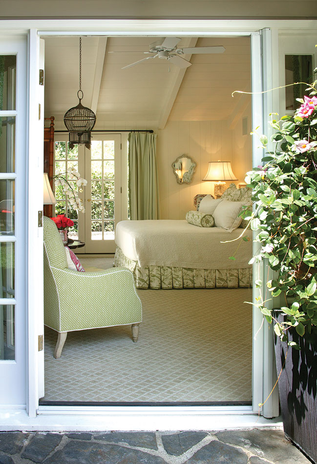 View from a patio in through French doors to a charming cottage bedroom with pastel green and cream accents.