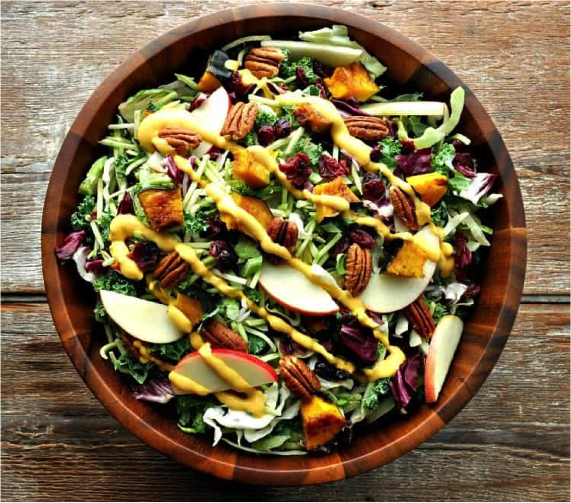 Fall Harvest Salad with Pumpkin Goddess Dressing in a wooden bowl