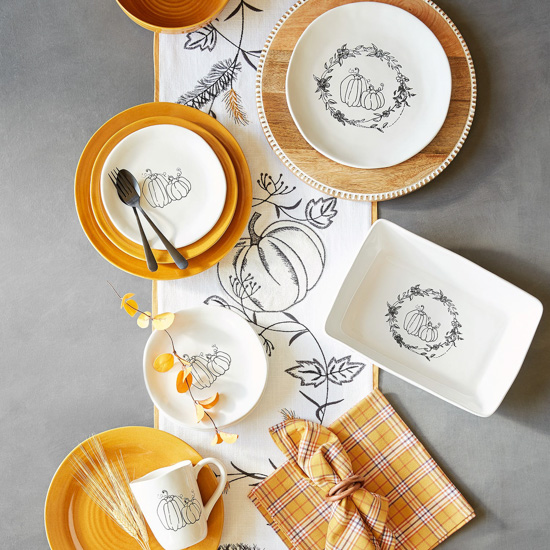 Aerial view of a display of Pier 1's Buffalo Harvest collection including mugs, plates and serve ware with a simplistic pumpkin line design on white dishes.