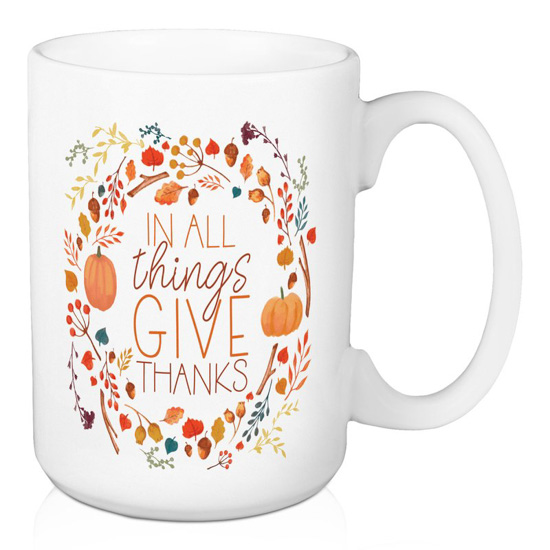 "White porcelain mug with ""in all things give thanks"" written and encircled by fall foliage."