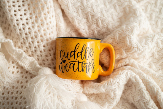 "Cream colored blankets on the background and a ceramic, mustard colored, camp style mug that says ""cuddle weather""."