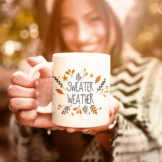"Girl in nature holding out a white mug that says ""sweater weather"" surrounded by fall colored leaves."