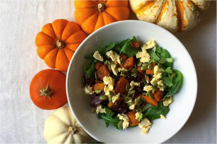 Fall Squash Salad with Maple Wine Vinaigrette in a white bowl surrounded by mini pumpkins
