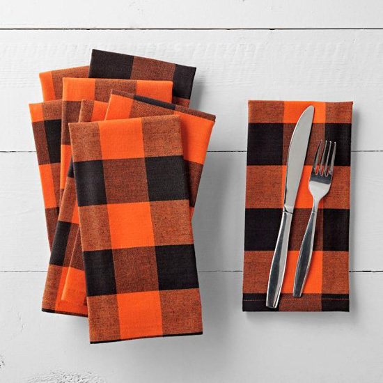 Stack of orange and black buffalo checked cloth napkins and one folded one to the right set with silverware on it.