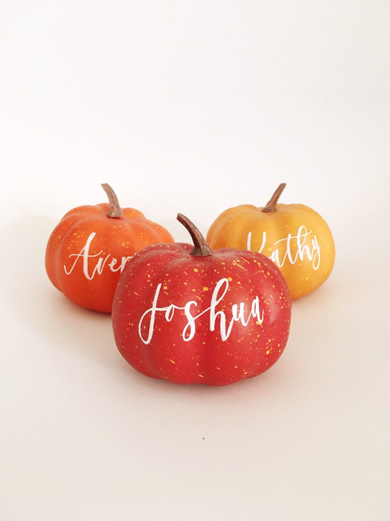 Plastic pumpkins in a variety of colors with hand lettered names written on them as placeholders.