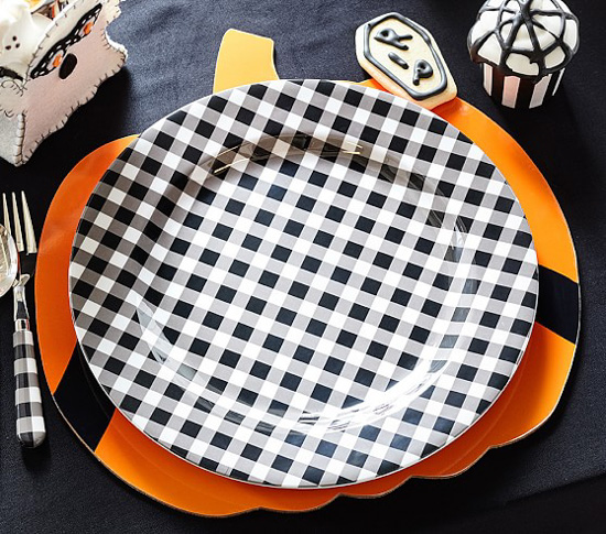 Pumpkin shaped charger topped with a gingham dinner plate next to a gingham handles for and some spooky halloween desserts.