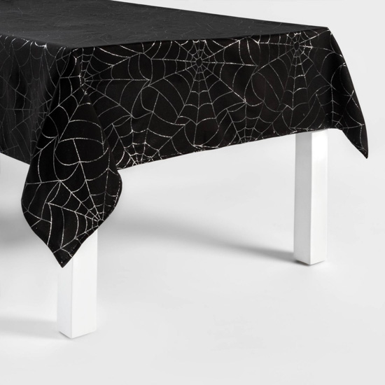 White legged dining table covered in a black tablecloth with metallic silver spider web design.