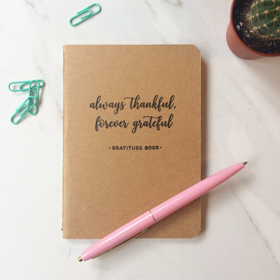 "Kraft paper covered brown notebook that says, always thankful, forever grateful"" on the cover placed with a pink pen, small paperclips and a planted cactus."