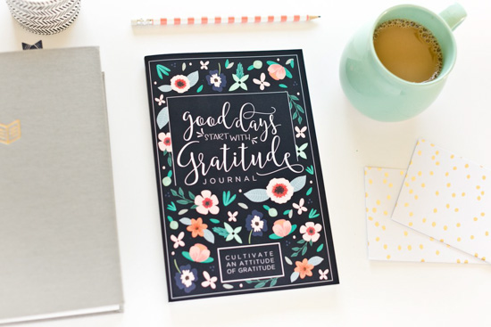 Gratitude journal placed next to a pencil, coffee mug, and notebooks.
