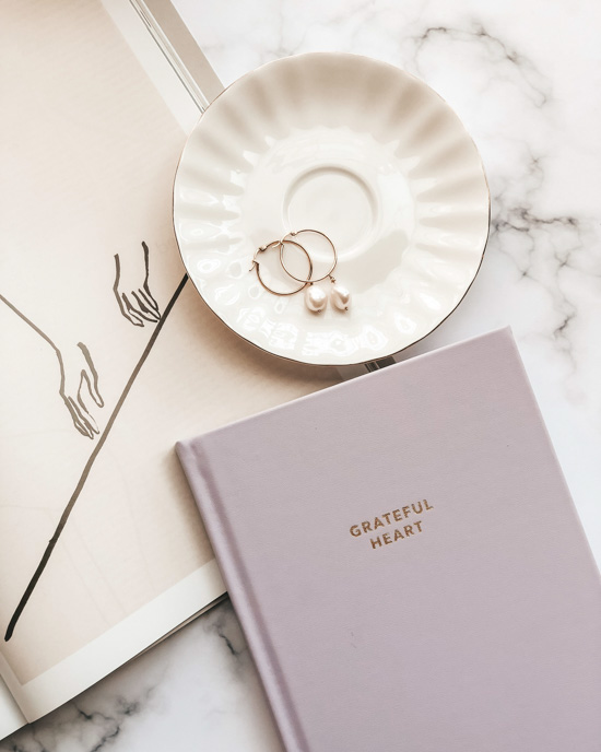 "Pink hardcover journal that says ""grateful heart"" on the cover next to an open book and a porcelain dish with pearl earrings in it."