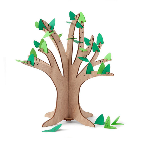 Small standing wooden tree with small slits for finding slips of green paper in them to make leaves.