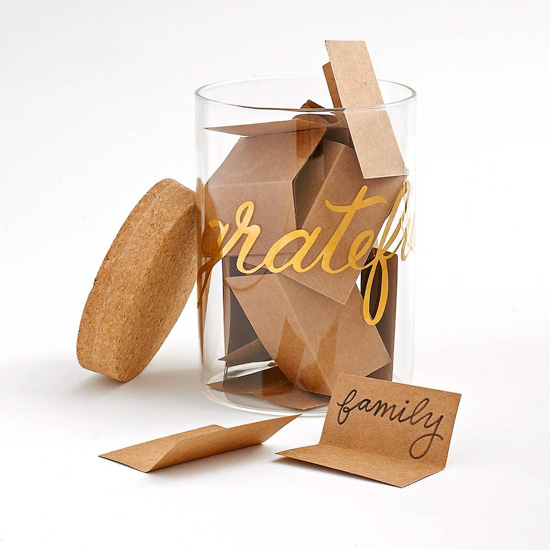 "Glass jar with ""grateful"" written around the outside in gold calligraphy, filled with Kraft paper notes of thankfulness with a cork lid."