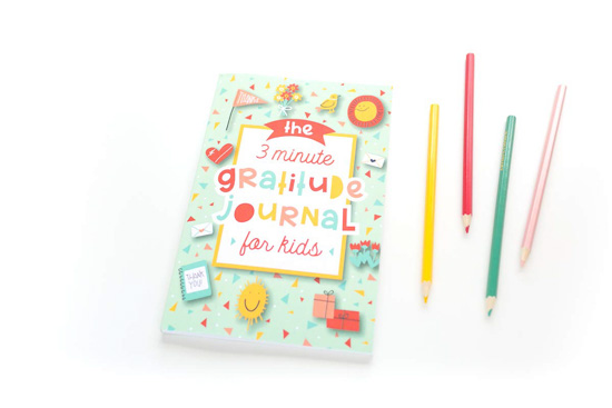 3 minute gratitude journal for kids next to 4 colored pencils that match the book's color scheme.
