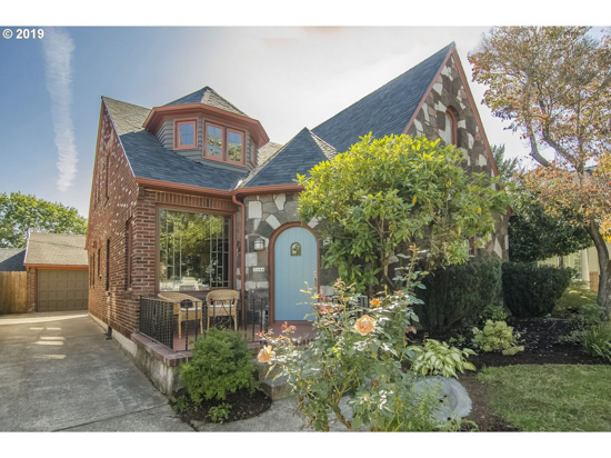 Storybook Cottage front elevation with charming roof lines and a light blue front door.