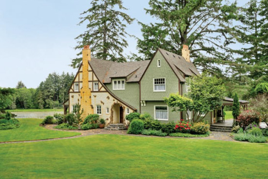Storybook style cottage in on expansive green grass with mature trees in the background.