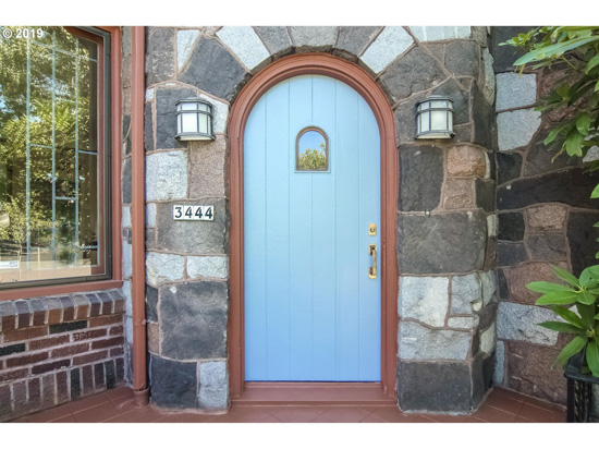 Stone covered front cottage entryway with a rounded light blue front door.