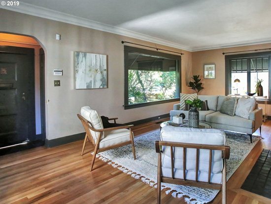 Charming bungalow living room and front door entry with large window letting in light and midcentury modern designed seating around a white rug.