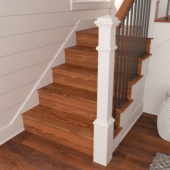 White and metal banister and the bottom portion of a staircase, displaying new wooden stair risers stained to match the wooden floors of the home.