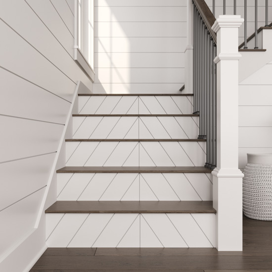 View from the bottom of a staircase displaying new white shiplap stair risers.