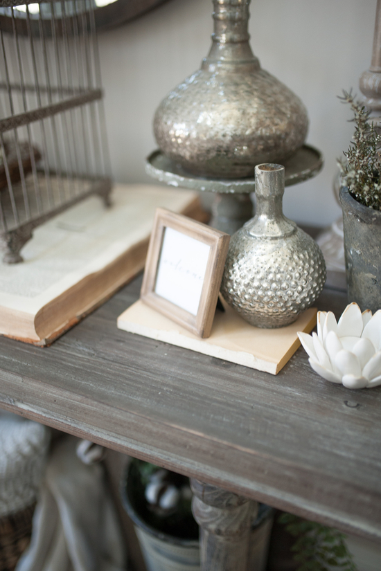 Entryway table topped with small trinkets like metal vases, porcelain lotus flowers and a fresh plant.