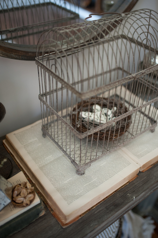 An vintage book laying open on an entryway table and topped with an antique birdhouse filled with a faux nest.
